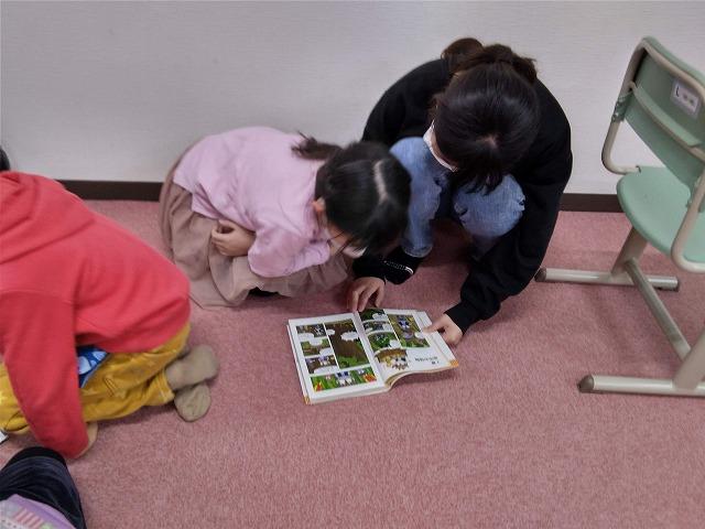 新しい本をスタッフと読む子ども